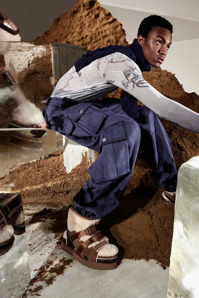 Model working, with a backdrop of dirt and block ice, wearing UGG boots by Feng Chen Wang.
